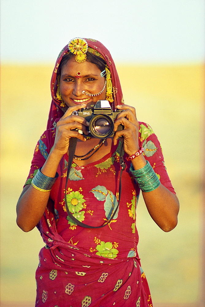 Portrait of indigenous woman holding tourist's camera, Thar Desert, near Jaisalmer, Rajasthan, India, Asia