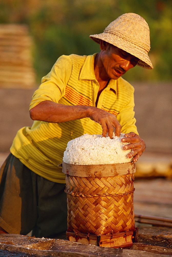 Portrait of a man piling salt into a basket on the east coast of the island of Bali, Indonesia, Southeast Asia, Asia
