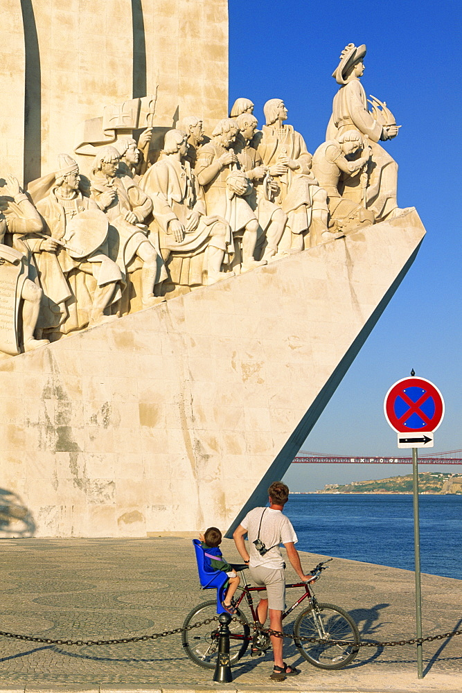 Father and son on a bicycle in front of the Monument of the Discoveries (Padrao dos Descobrimentos) inaugurated in 1960, by the Tejo River in Lisbon, Portugal, Europe