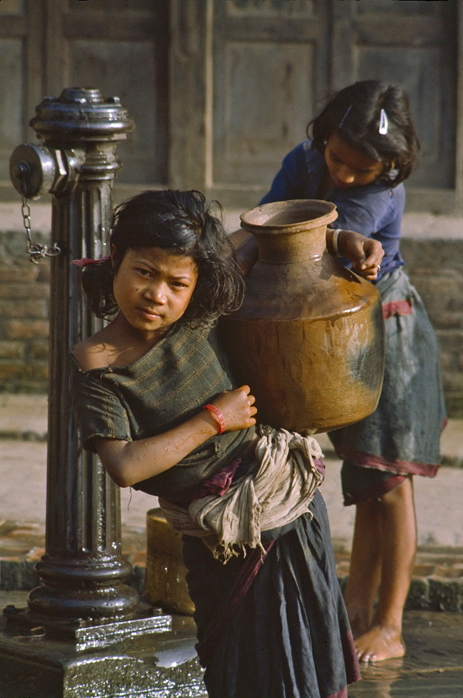 Girl carrying water bottle in Bhaktapur, Nepal, Asia