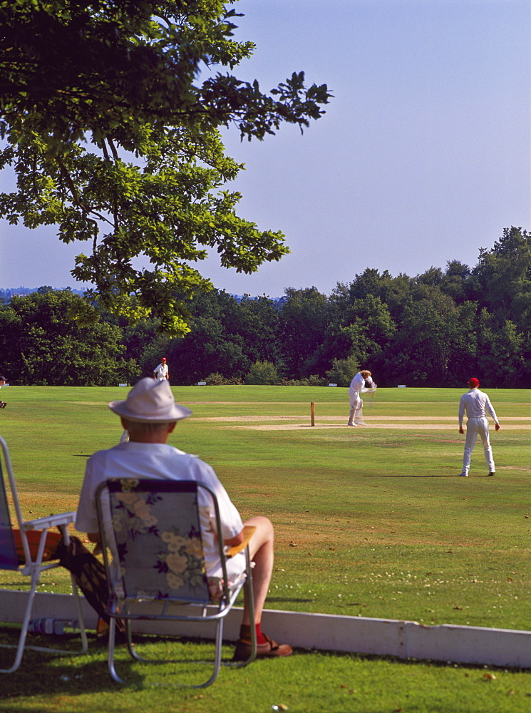 Man watching a game of cricket on Southborough Common, near Tunbridge Wells, Kent, England, United Kingdom, Europe - 16-3287