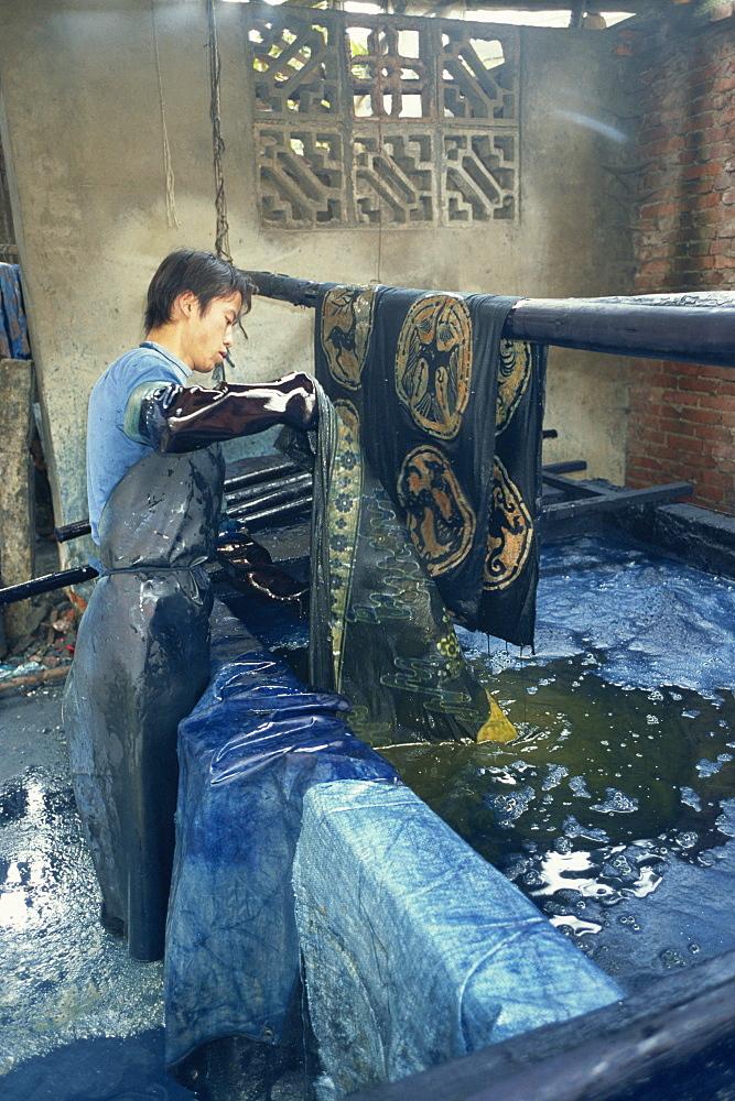 Dipping batik in an indigo vat, Guizhou, China, Asia - 188-6785