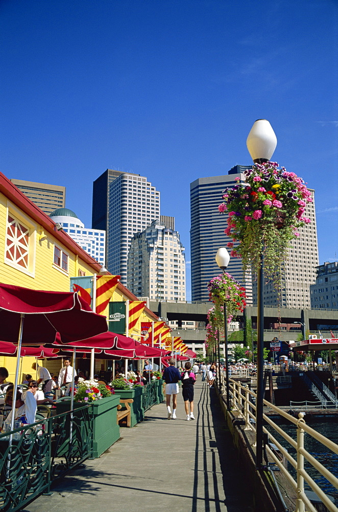 Cafes on Pier 56 on the waterfront with tower blocks of the city in the background, in Seattle, Washington State, United States of America, North America
