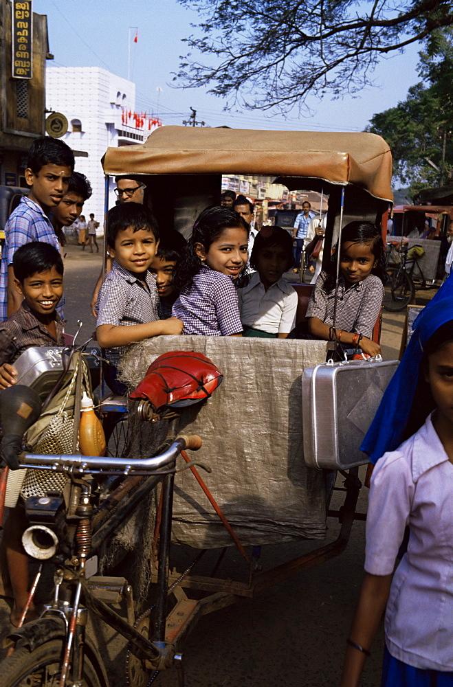 Schoolchildren in cycle rickshaw, Aleppey, Kerala state, India, Asia