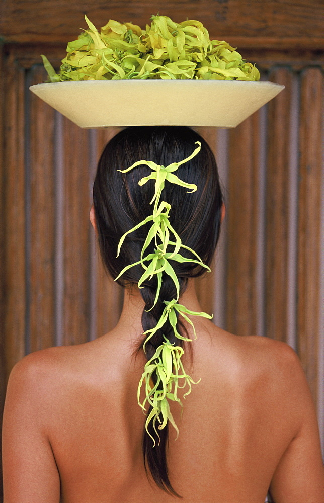 Back view of young woman with long hair balancing a bowl of ylang ylang on her head - 238-5177