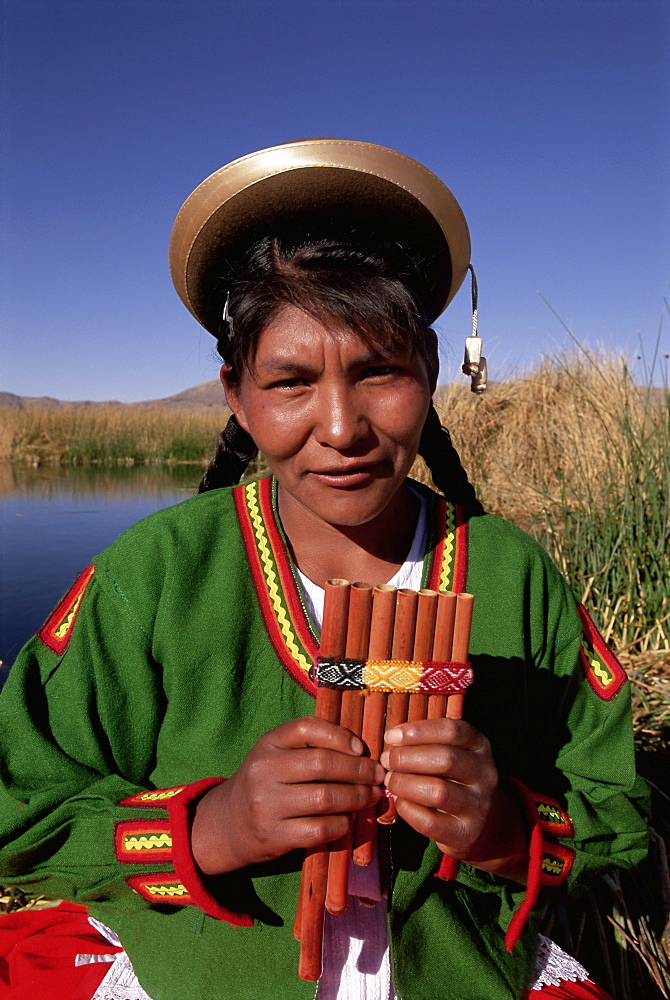 Head and shoulders portrait of a Uros Indian woman holding pipes, on floating reed island, Islas Flotantes, Lake Titicaca, Peru, South America