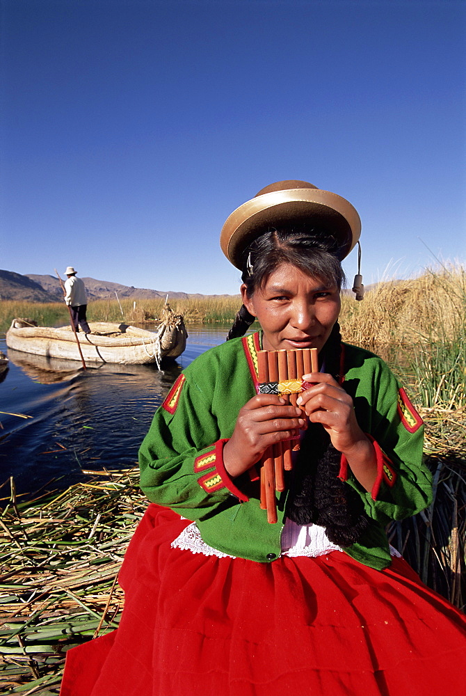 Portrait of a Uros Indian woman holding pipes, on floating reed island, Islas Flotantes, Lake Titicaca, Peru, South America