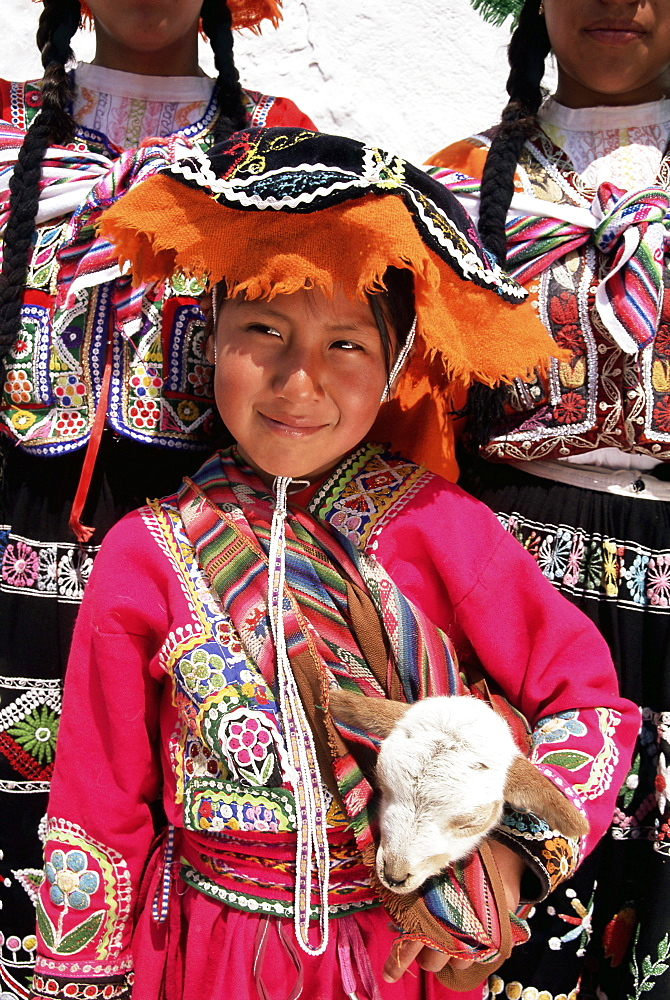 Portrait of a local smiling Peruvian girl in traditional dress, holding a young animal, Cuzco, Peru, South America