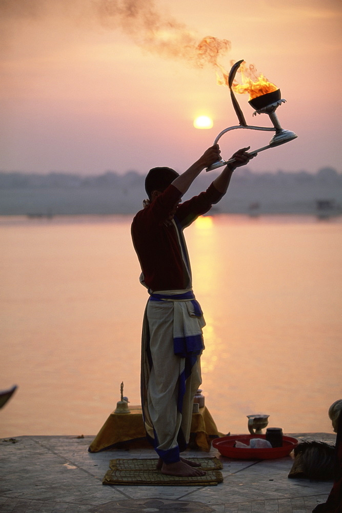 Hindu man worshipping in front of setting sun, River Ganges (Ganga), Varanasi (Benares), Uttar Pradesh state, India, Asia