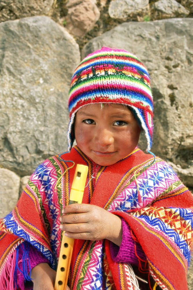 Portrait of a Peruvian boy in a knitted hat, playing the flute, near Cuzco, Peru, South America