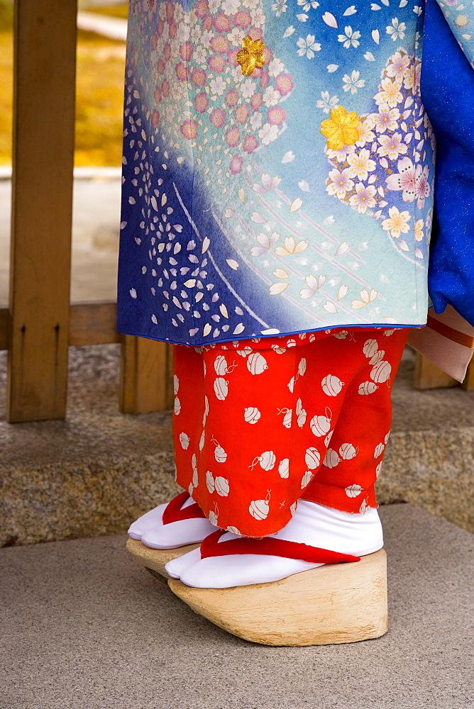 Maiko (apprentice geisha) wearing traditional Japanese kimono and okobo (tall wooden shoes), Kyoto, Kansai region, island of Honshu, Japan, Asia - 252-10940