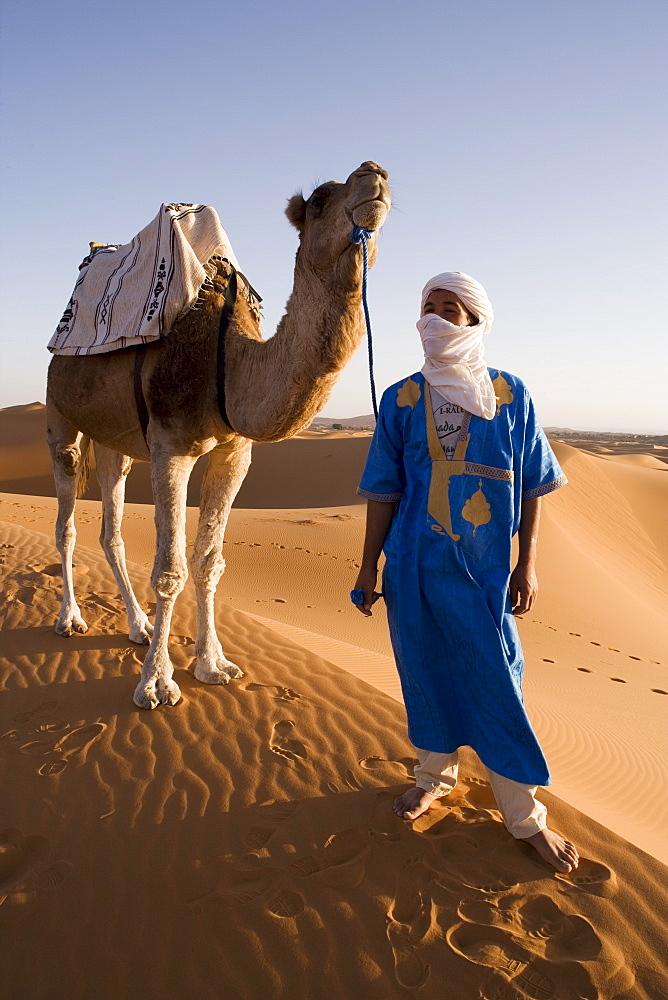 Berber man standing with his camel, Erg Chebbi, Sahara Desert, Merzouga, Morocco, North Africa, Africa