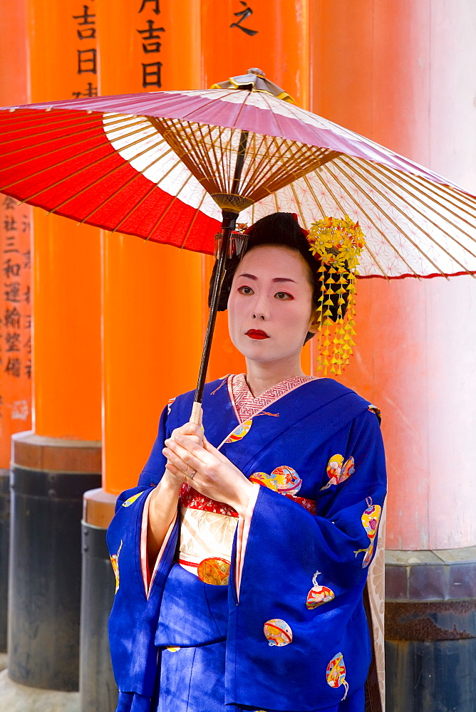 Portrait of a geisha holding an ornate red umbrella in front of a line of red torii gates, Fushimi-Inari Taisha, Kyoto, Kansai Region, Honshu, Japan, Asia - 252-11345