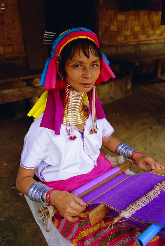 Portrait of a 'Long necked' Padaung tribe woman weaving on a hand held loom, Mae Hong Son Province, northern Thailand, Asia