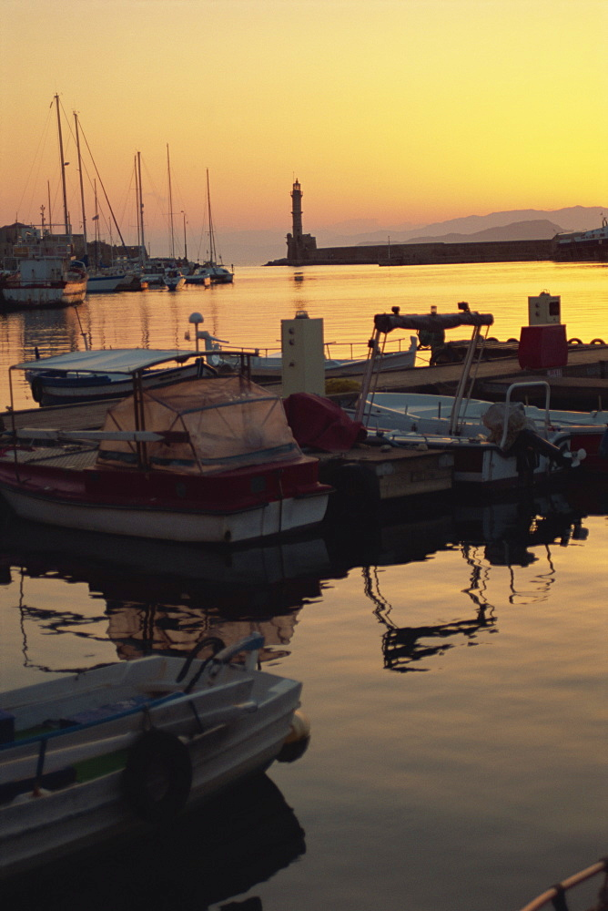 Dusk light over moored boats in the harbour and the lighthouse silhouetted on the horizon, Chania, Crete, Greece, Europe