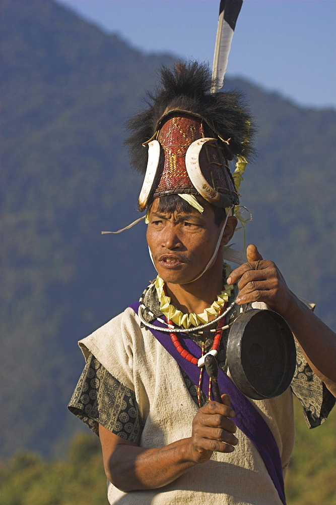 Naga man dancing and playing musical instrument, wearing headdress made of woven cane decorated with wild boar's teeth, bear fur and topped with hornbill feather, Naga New Year Festival, Lahe village, Sagaing Division, Myanmar (Burma), Asia