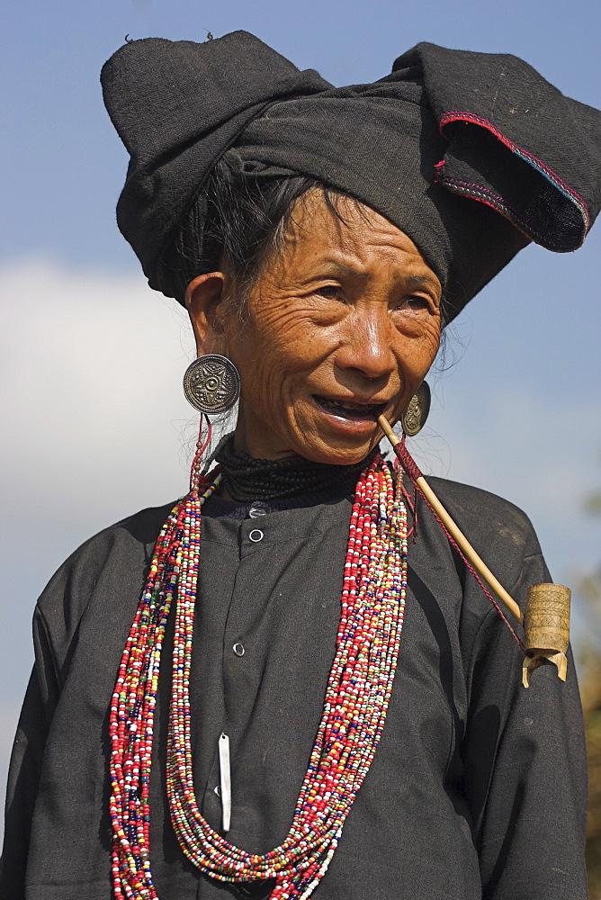 Aku lady smoking wooden pipe, Wan Sai village, Kengtung (Kyaing Tong), Shan state, Myanmar (Burma), Asia