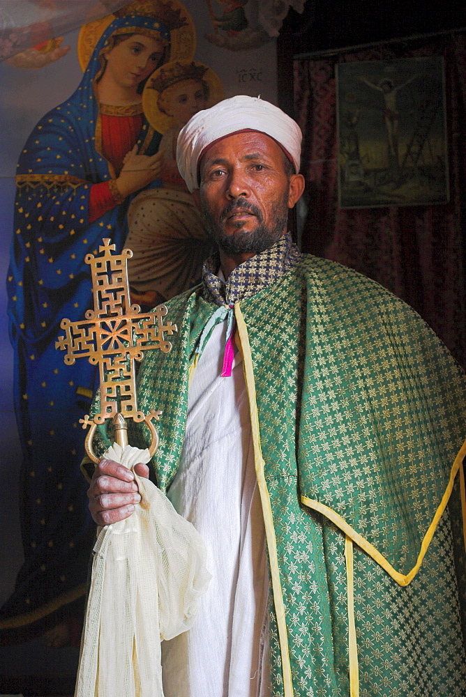 Stock photo of Priest with cross, Bet Meskel, an excavated chapel in the northern wall of the courtyard of Bet Maryam