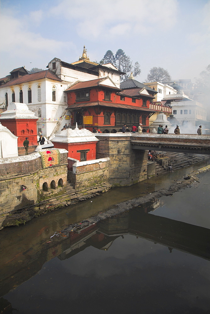 Smoke rising from cremation ceremony on banks of Bagmati River during Shivaratri festival, Pashupatinath Temple, UNESCO World Heritage Site, Kathmandu, Nepal, Asia