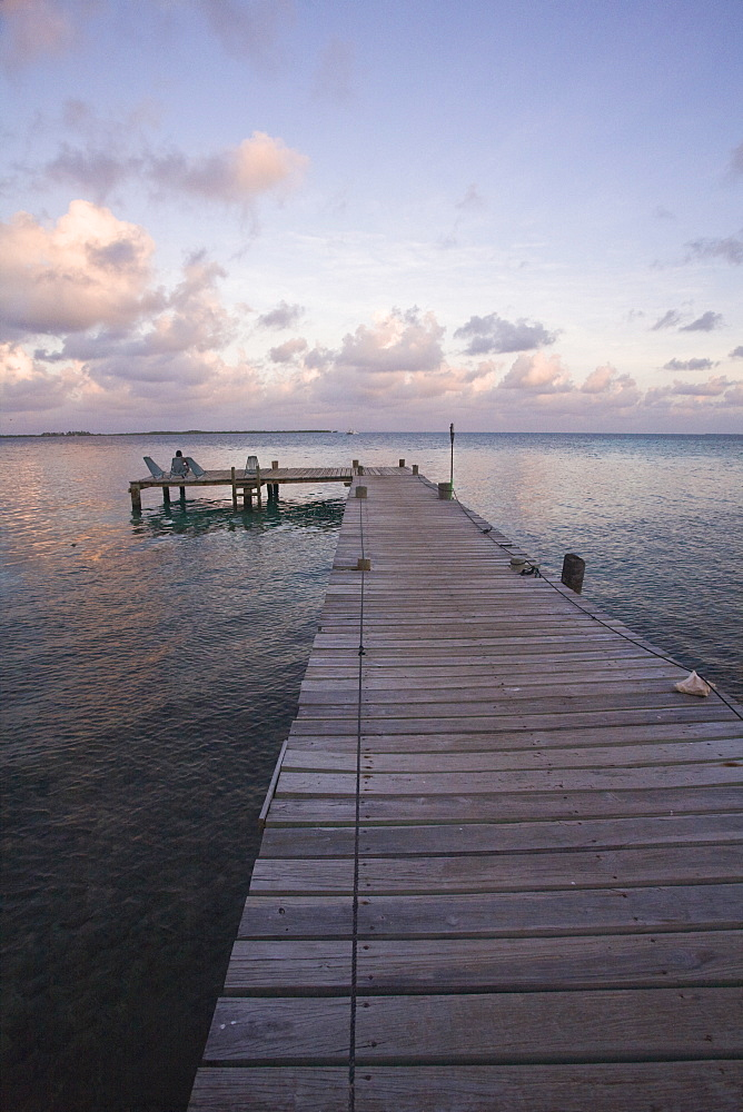 People sitting on chair on jetty at sunrise, Tobaco Caye, Belize, Central America