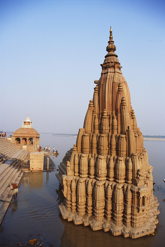 Partially submerged tilted Shiva temple below the ghats on the edge of the River Ganges (Ganga), Varanasi (Benares), Uttar Pradesh, India, Asia