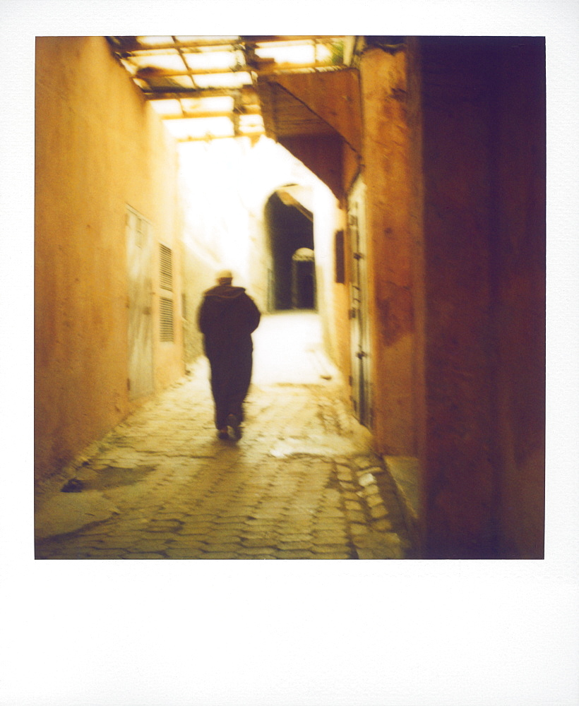 Polaroid image of man walking along narrow, dimly-lit street in the Medina, Fez, Morocco, North Africa, Africa