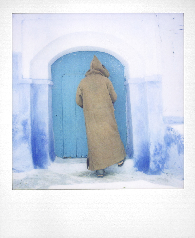 Polaroid of man wearing traditional woollen djellaba opening blue painted door to traditional house, Chefchaouen, Morocco, North Africa, Africa