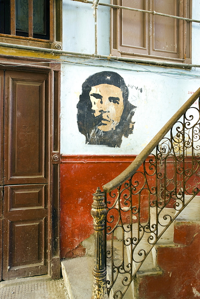 Faded mural of Che Guevara on the staircase of a dilapidated apartment building, Havana Centro, Havana, Cuba, West Indies, Central America