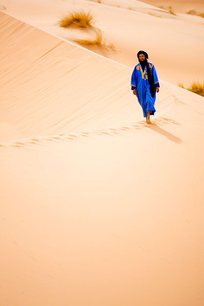 Berber man in blue robe walking along the ridge of a sand dune in the Erg Chebbi sand sea near Merzouga, Morocco, North Africa, Africa