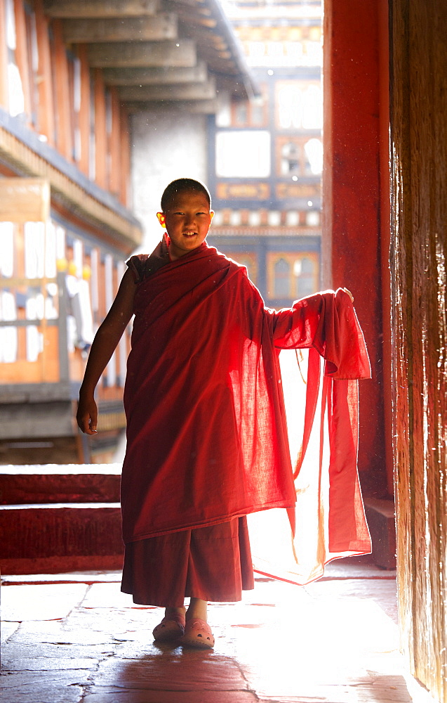 Young Buddhist monk in red robes backlit by evening sunlight at the Jakar Dzong, Jakar, Bumthang, Bhutan, Asia