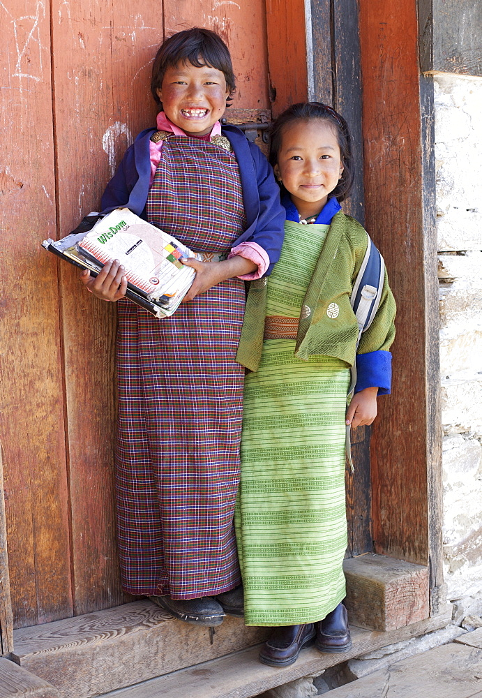 Two young girls, one holding school books, at their school in Ura Village, Ura Valley, Bumthang, Bhutan, Asia