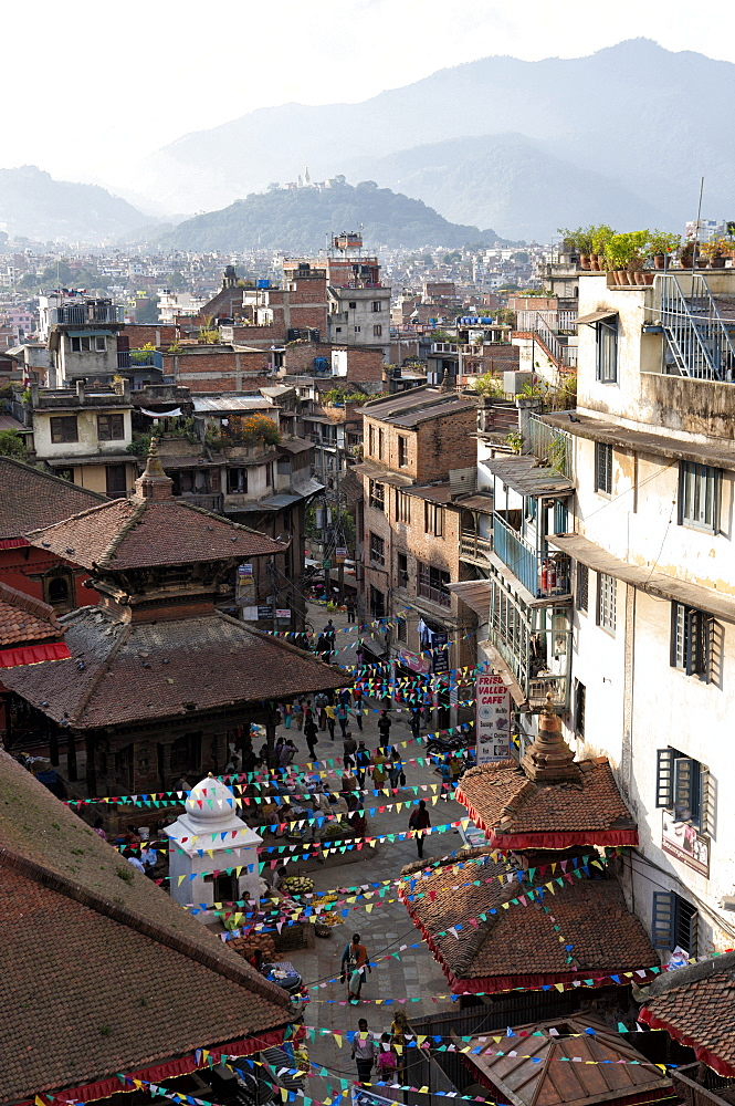 View over narrow streets and rooftops near Durbar Square towards the hilltop temple of Swayambhunath, Kathmandu, Nepal, Asia