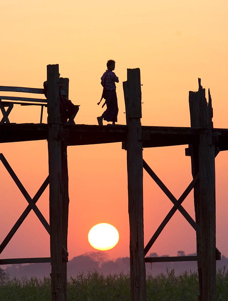 Local man walking on the famous U Bein teak bridge at sunset, near Mandalay, Myanmar (Burma), Asia