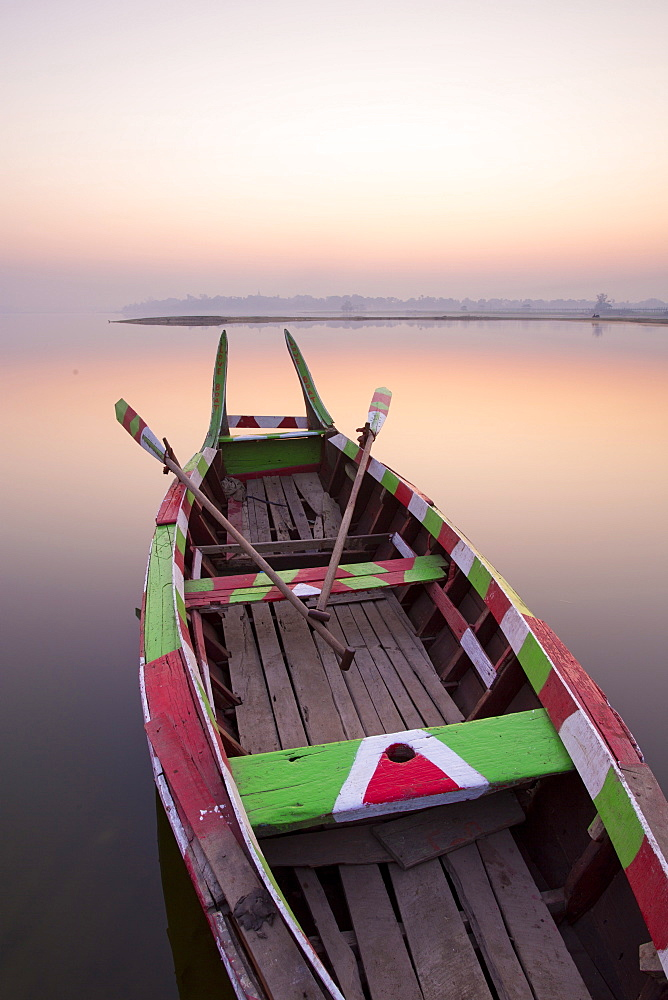 Traditional rowing boat moored on the edge of flat calm Taungthaman Lake at dawn with the colours of the sky reflecting in the calm water, close to the famous U Bein teak bridge, near Mandalay, Myanmar (Burma), Asia - 321-5101