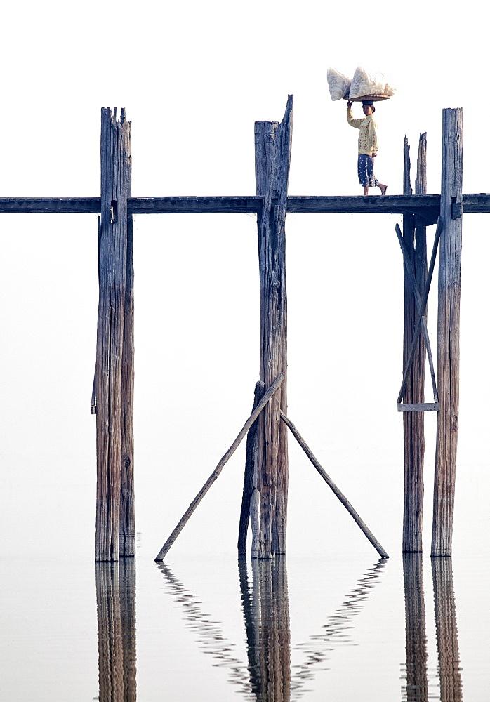 Local woman carrying goods on her head across U Bein Bridge, the world's longest teak foot bridge spanning 1300 yards over Taungthaman Lake, Amarapura, near Mandalay, Myanmar (Burma), Asia