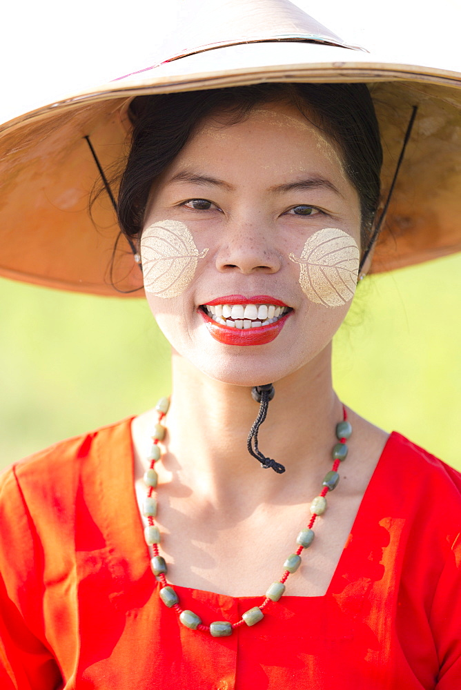 Portrait of local woman wearing traditional bamboo hat, red dress and Thanaka face painting in the shape of leaves on her cheeks, near Mandalay, Myanmar (Burnma), Asia