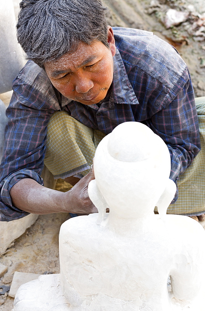 Local man carving a marble Buddha image using an angle grinder, and covered in white marble dust, stone carver's district, Amarapura, near Mandalay, Myanmar (Burma), Southeast Asia