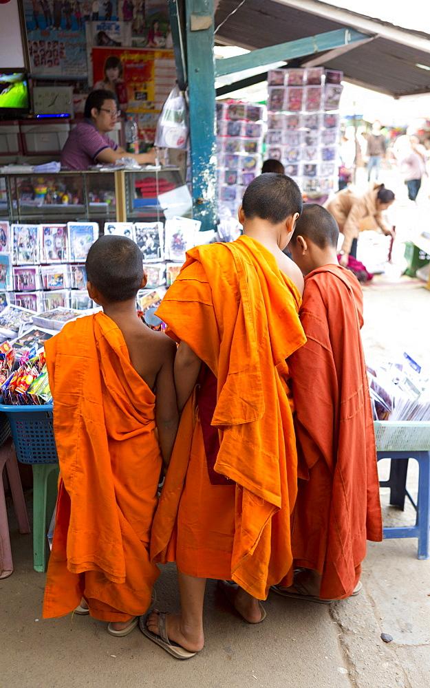 Three novice monks buying comics in the town market, Kengtung (Kyaingtong), Shan State, Myanmar (Burma), Asia