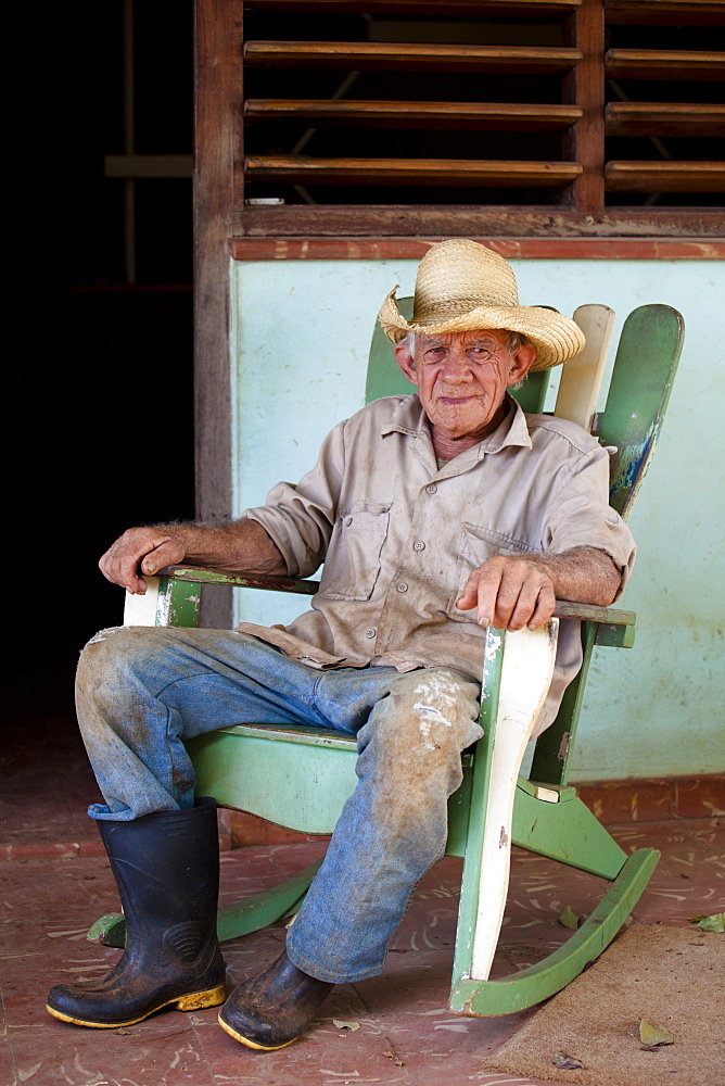 Tobacco farmer wearing straw hat and Wellington boots, on a rocking chair outside his house, Vinales, Pinar Del Rio, Cuba, West Indies, Central America