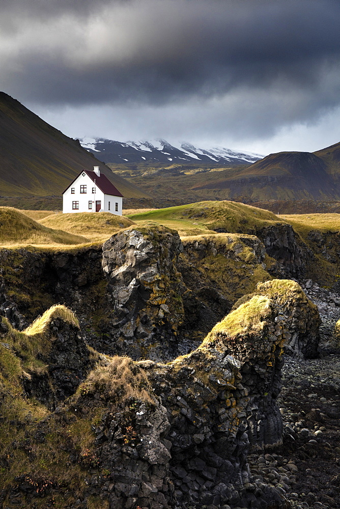 Lone house and sea stacks in stormy weather, Arnastapi, Snaefellsnes Peninsula, Iceland, Polar Regions