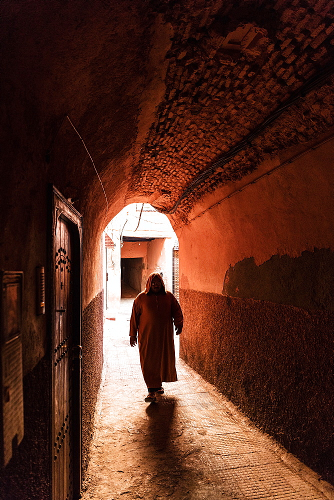 Local man dressed in traditional djellaba walking through archway in a street in the Kasbah, Marrakech, Morocco, North Africa, Africa - 321-5853