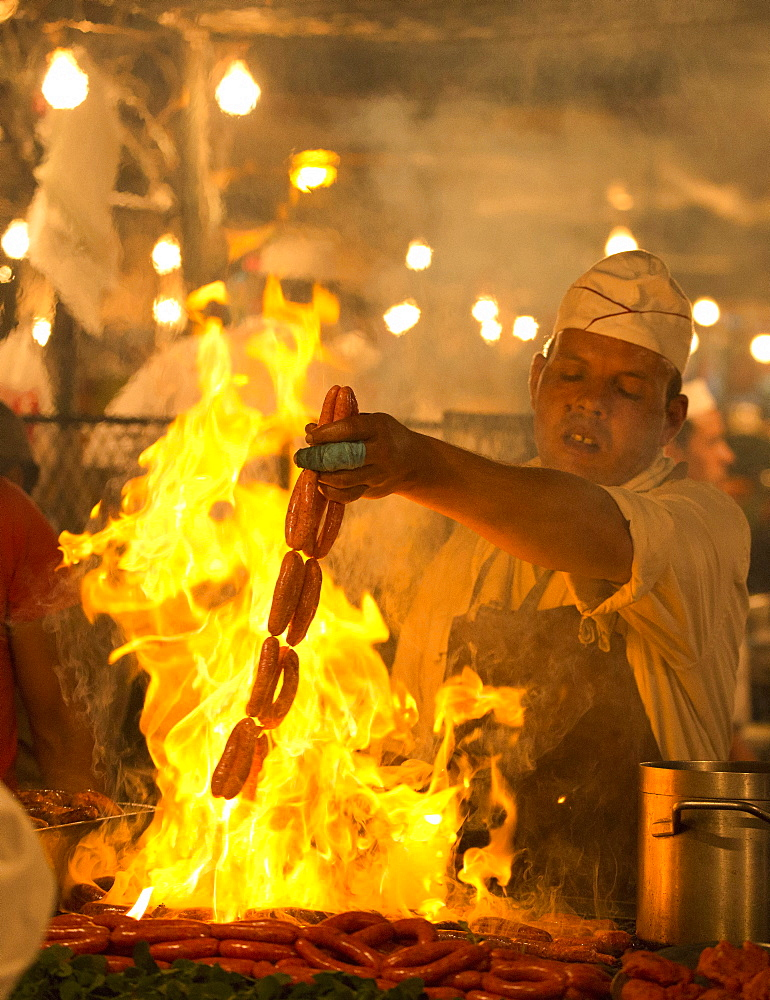 Local man cooking sausages on open flame at one of the food stalls in the Djemaa el Fna, Marrakech, Morocco, North Africa, Africa - 321-5859