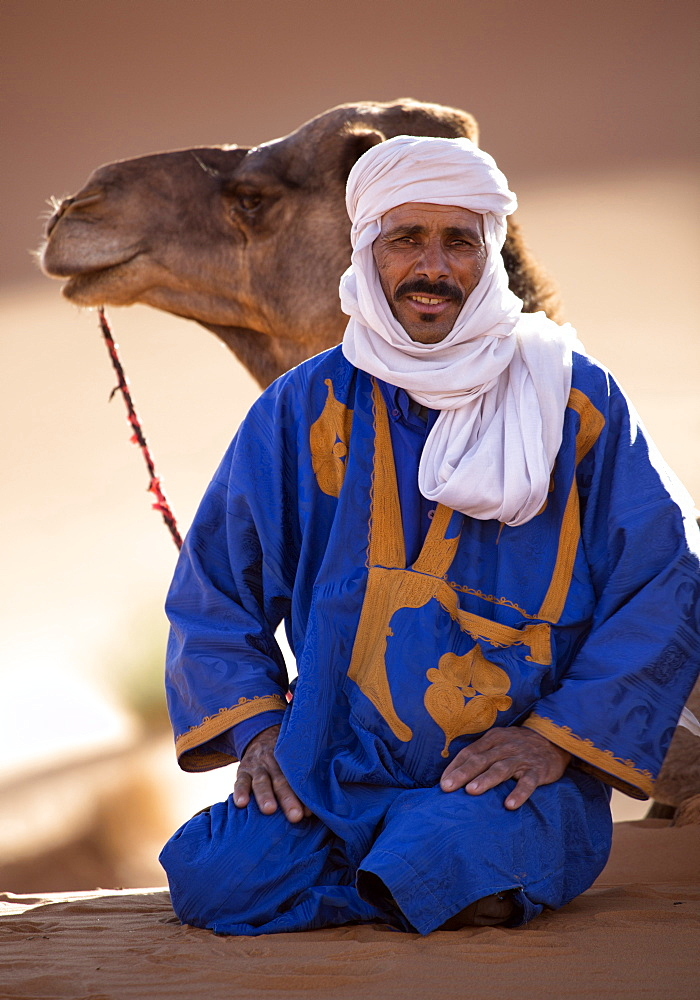 Berber man with camel, resting in the Erg Chebbi Sand sea, part of the Sahara Desert near Merzouga, Morocco