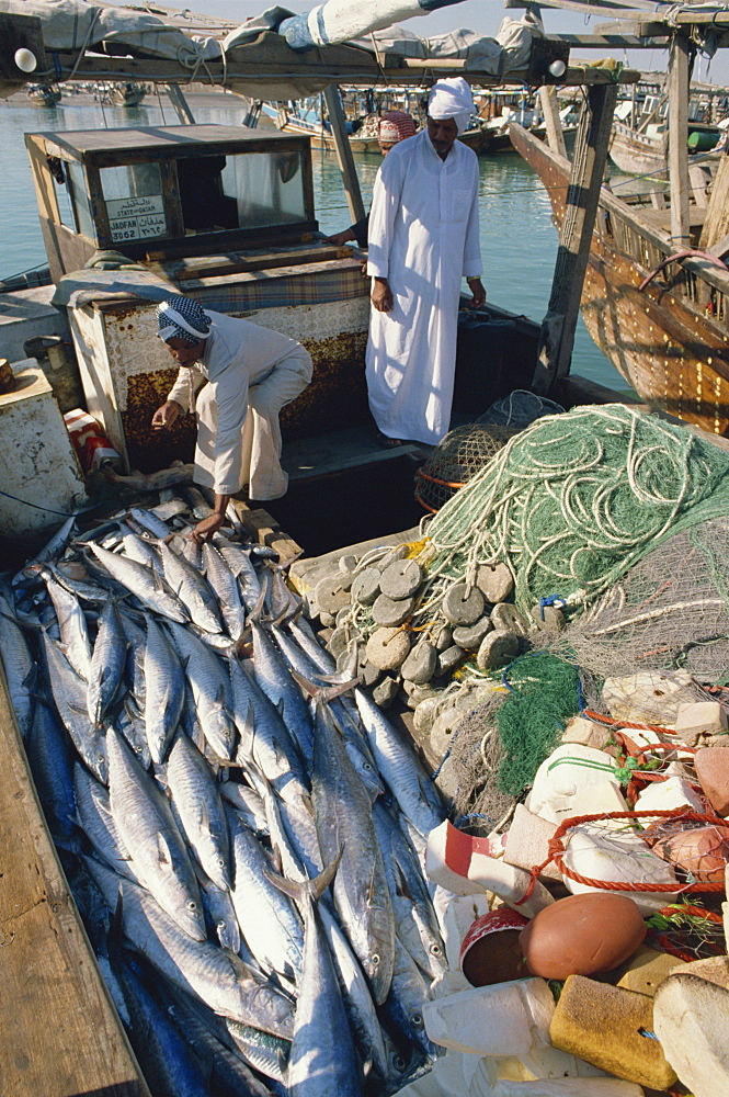 Men on fishing boat with catch, Qatar, Middle East