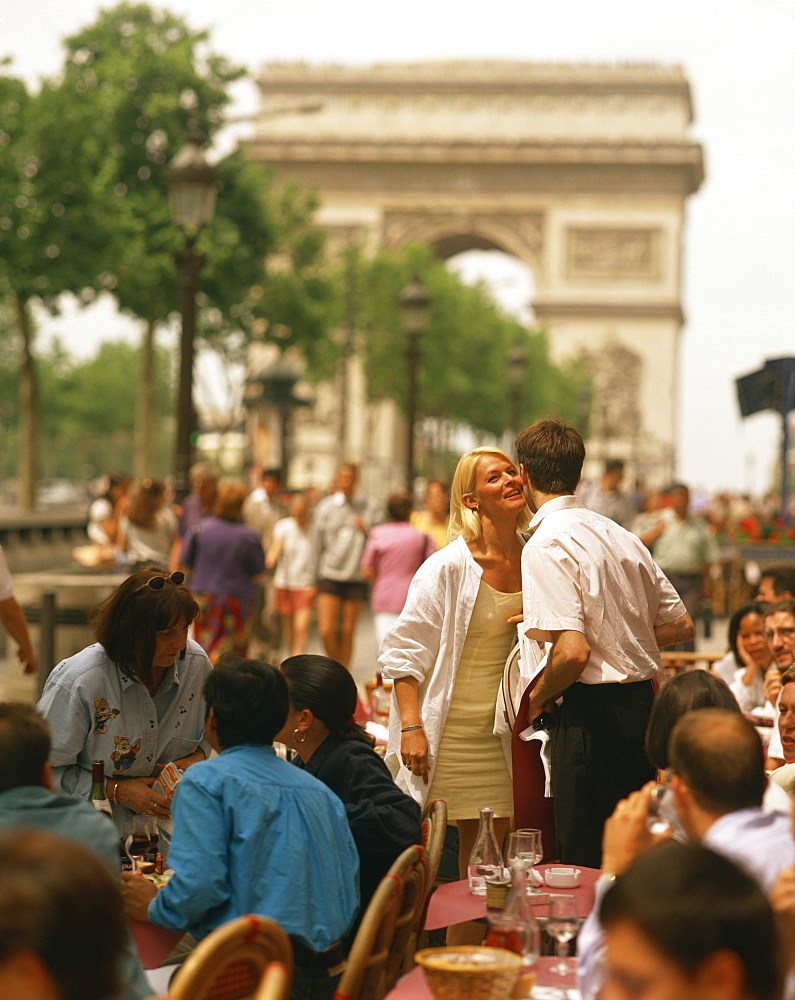 Greeting friends at an outdoor cafe on the Champs Elysees with the Arc de Triomphe behind, Paris, France, Europe