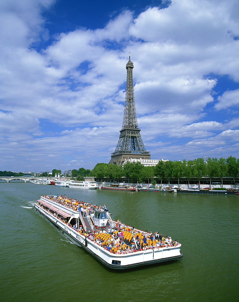 Tourists on bateau mouche on the River Seine with the Eiffel tower in the background, in Paris, France, Europe