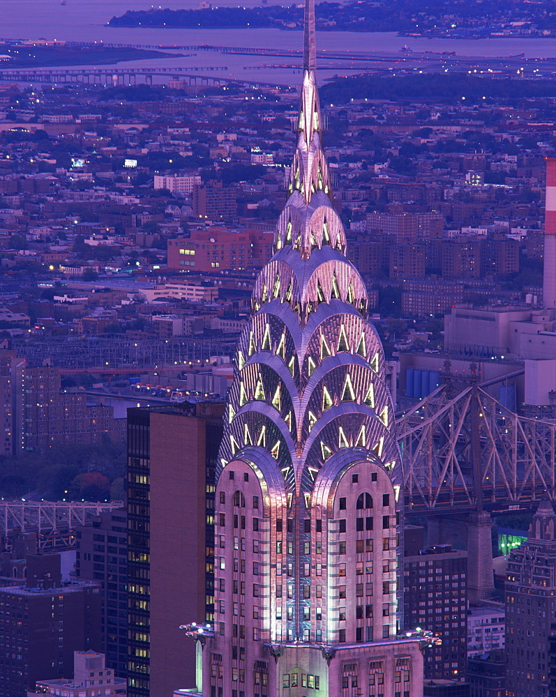 The top of the Chrysler Building illuminated in the evening with a bridge and the city of New York in the background, United States of America, North America