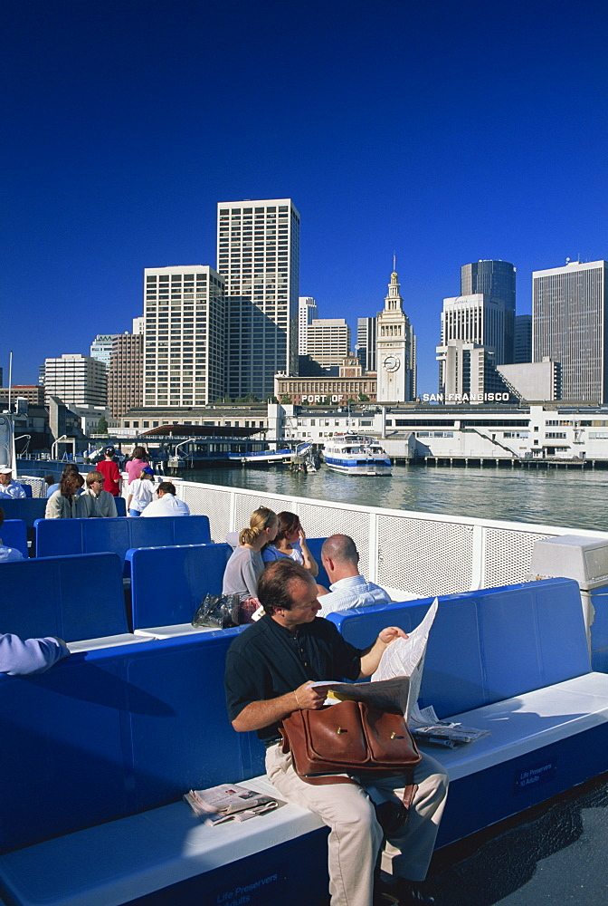 Man reading newspaper and passengers on the commuter ferry, with Ferry Building and skyline of downtown San Francisco in the background, California, United States of America, North America