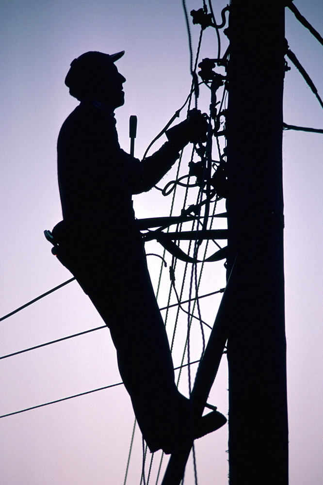 Silhouette of engineer working up a telegraph pole, East Sussex, England, United Kingdom, Europe
