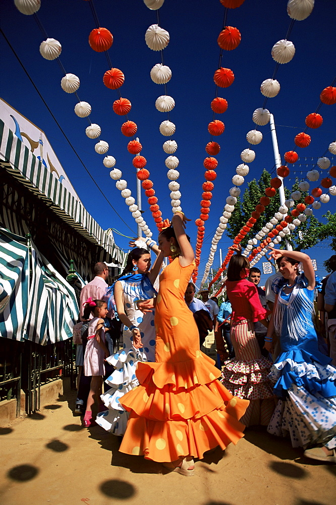 Girls dancing a sevillana beneath colourful lanterns, Feria de Abril (April Fair), Seville, Andalucia (Andalusia), Spain, Europe - 390-2491
